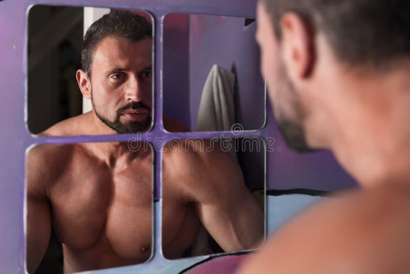 Stilig shirtless framsida för muskelmanwash i badrumspegeln arkivfoto