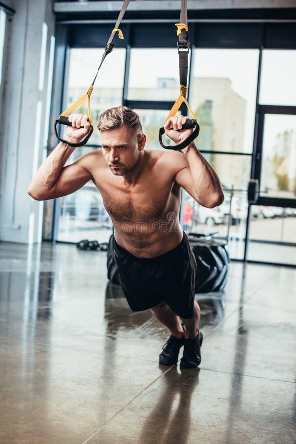 stilig shirtless idrottsman som övar med motståndsmusikband royaltyfria bilder