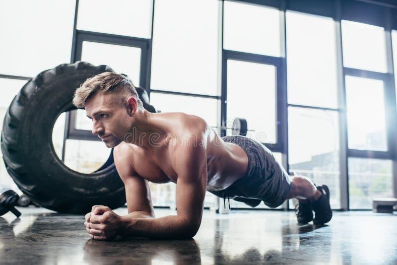 stilig shirtless idrottsman som gör plankan arkivbild