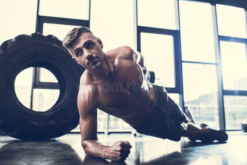 stilig shirtless idrottsman som gör plankan på en hand arkivbilder