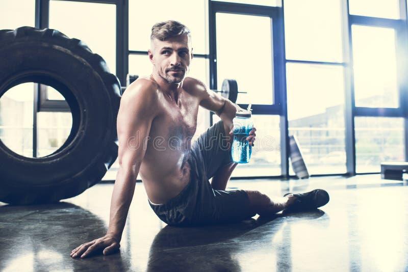 stilig shirtless idrottsman som sitter på golv i idrottshall och arkivfoto