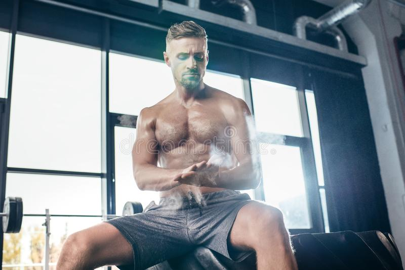 stilig shirtless idrottsman som sitter på gummihjulet och applicerar talkpulver på händer royaltyfria foton