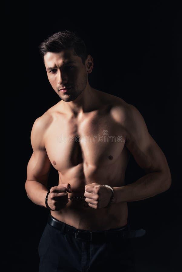 stilig shirtless man i handbojor som ser den isolerade kameran royaltyfri bild