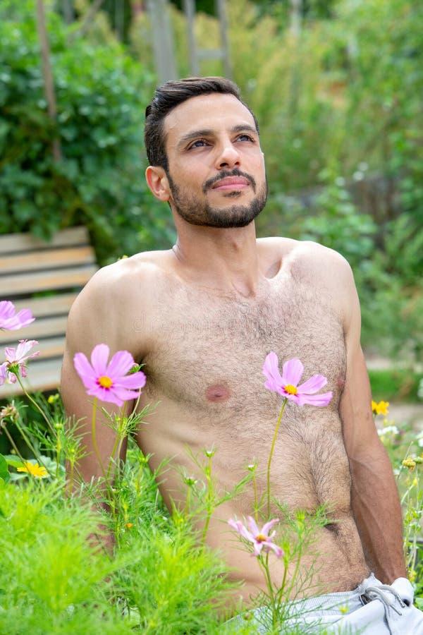 Stilig shirtless man med skägget som sitter utanför i trädgård arkivfoton