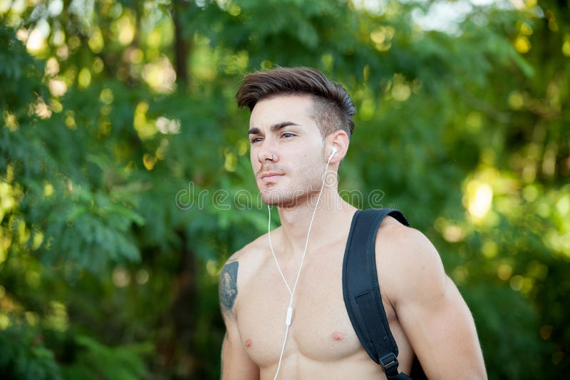 Stilig shirtless man som gör att fotvandra, medan lyssna till musik arkivbilder