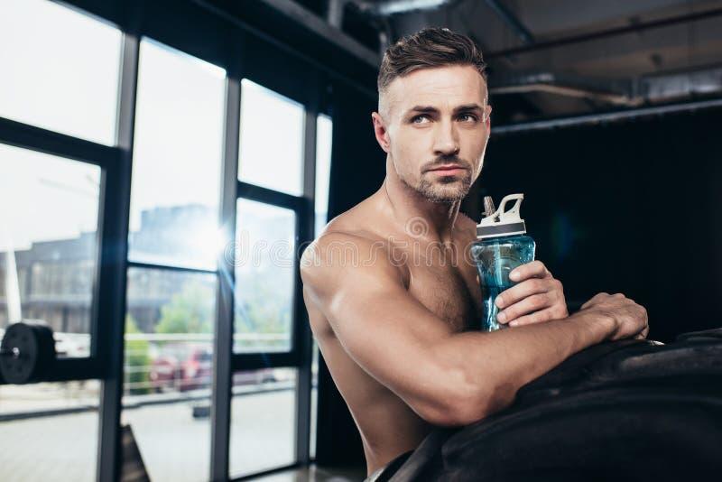 stilig shirtless muskulös idrottsman som lutar på gummihjulet och rymmer sportflaskan royaltyfri fotografi