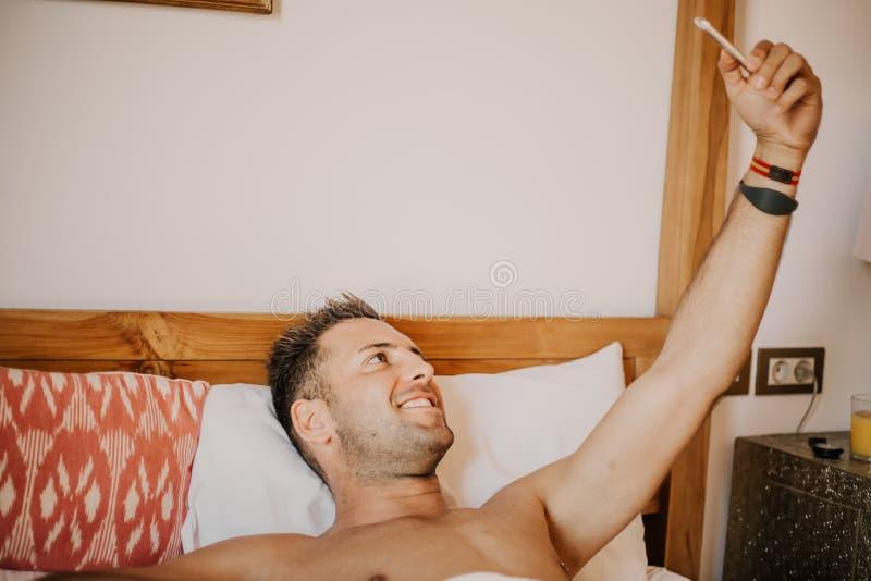 Stilig shirtless muskulös kroppsbyggareman i jeans som tar selfie med mobiltelefonen, medan lägga på säng sexigt barn för man royaltyfri bild
