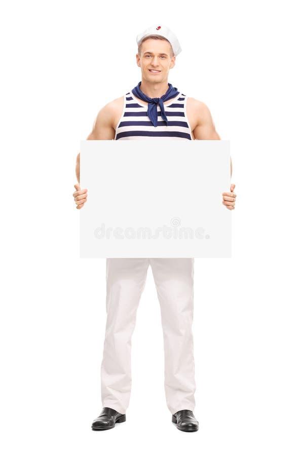 Stilig sjöman som rymmer ett tomt baner royaltyfri foto
