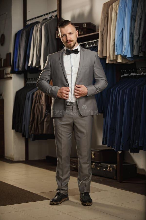 Stilig skäggig affärsman i klassisk dräkt Mannen i klassisk väst mot rad av dräkter shoppar in arkivbilder