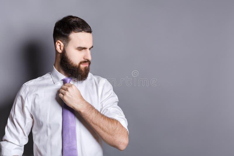 Stilig skäggig affärsman som justerar hans band arkivbilder