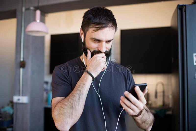 Stilig skäggig grabb som bär tillfällig grå t-skjorta lyssnande musik i hörlurar som kontrollerar sociala nätverk på smartphonen fotografering för bildbyråer