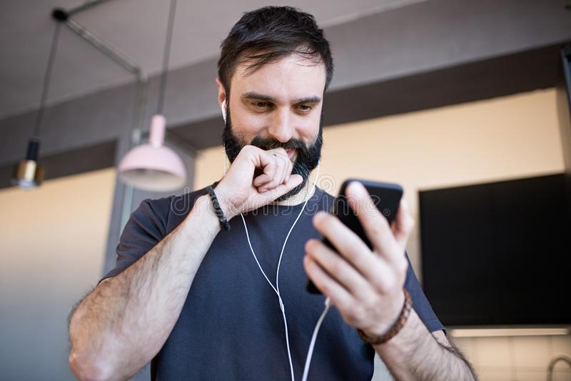 Stilig skäggig grabb som bär tillfällig grå t-skjorta lyssnande musik i hörlurar som kontrollerar sociala nätverk på smartphonen arkivbilder