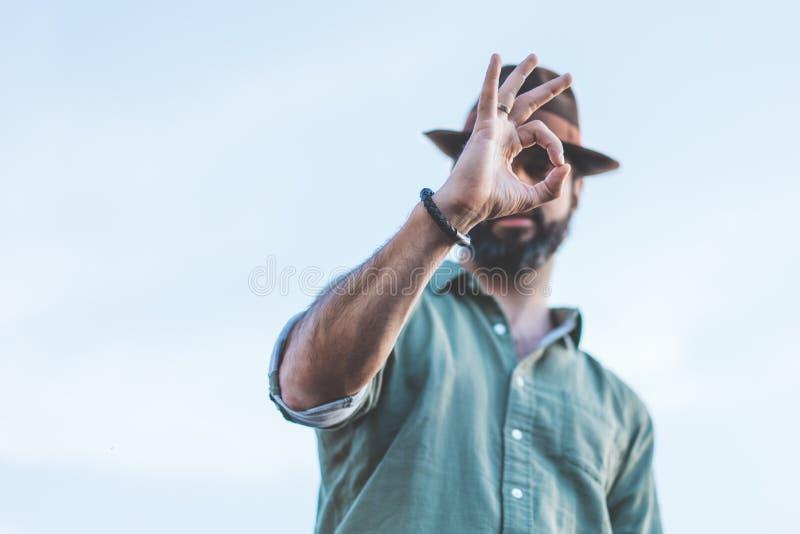 Stilig skäggig hipster som ser kameran till och med hans fingrar i ok gest Hållande ögonen på begrepp för folk arkivfoton