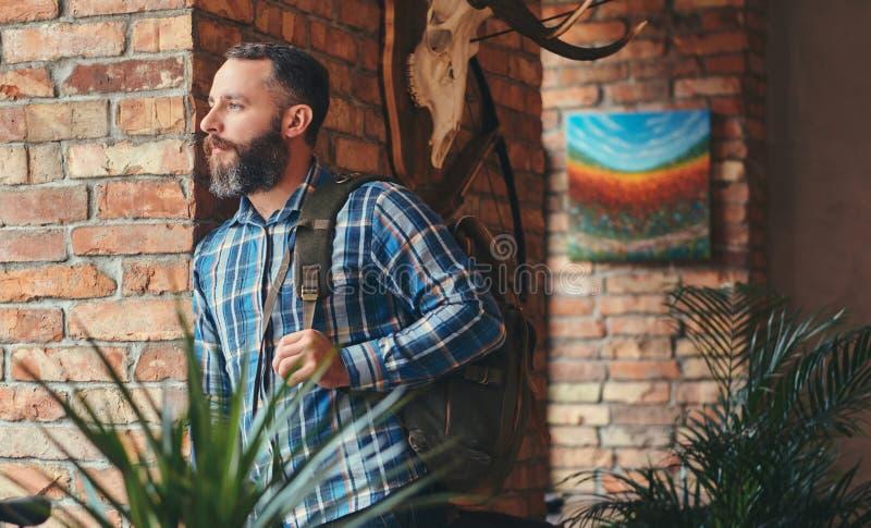 Stilig skäggig hipsterman i en blå ullbeklädnadskjorta och jeans med ryggsäckbenägenhet mot en tegelstenvägg på en studio arkivbilder