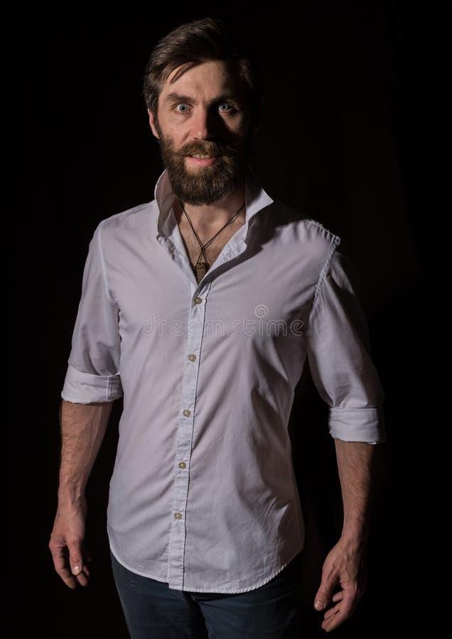 Stilig skäggig man för stående, sexig grabb på en mörk bakgrund royaltyfri fotografi