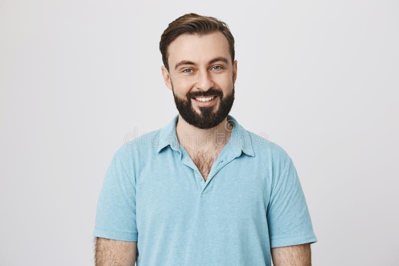 Stilig skäggig man i blå t-skjorta på en vit bakgrund Bartendern inviterar besökare med ett brett leende på hans framsida till royaltyfri fotografi