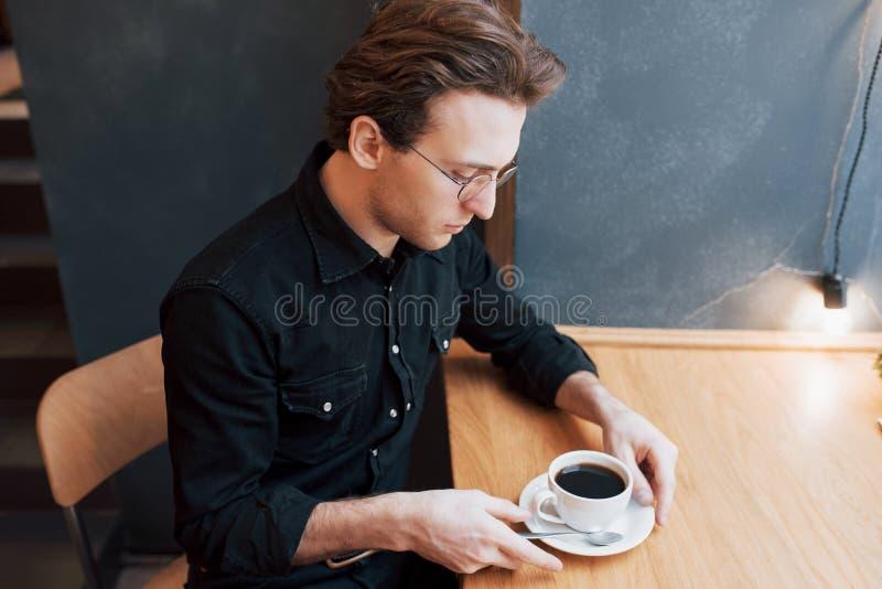 Stilig skäggig man i kontrollerad skjortainnehavgaffel som äter, i kafé och att le arkivfoton