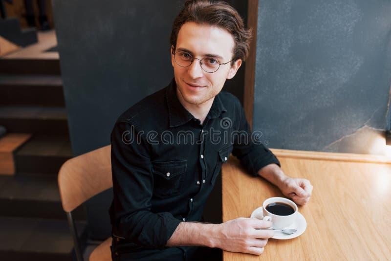 Stilig skäggig man i kontrollerad skjortainnehavgaffel som äter i kafé och ler se kameran royaltyfri foto