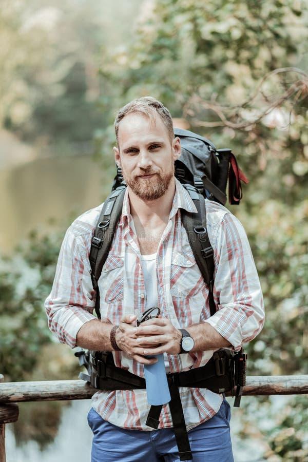 Stilig skäggig man med den tunga turist- ryggsäckinnehavflaskan av vatten royaltyfri fotografi