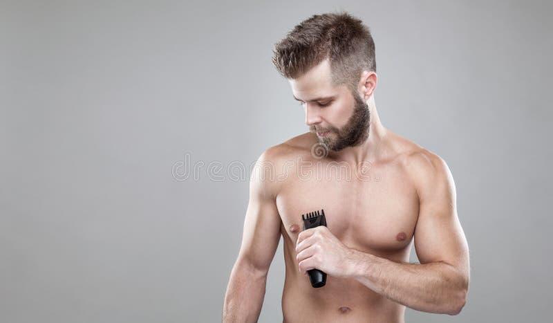 Stilig skäggig man med en beskärare som rakar av kropphår arkivfoto