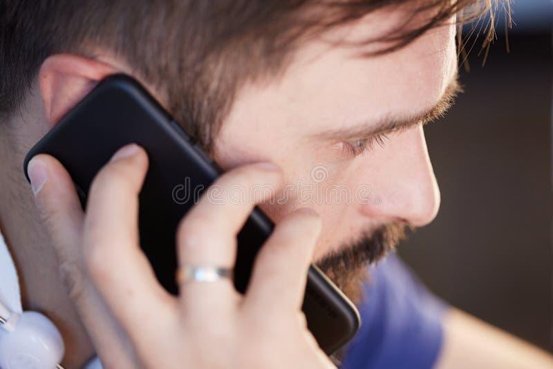 Stilig skäggig man som använder den mobila smartphonen på kontoret suddighet bakgrund arkivfoton