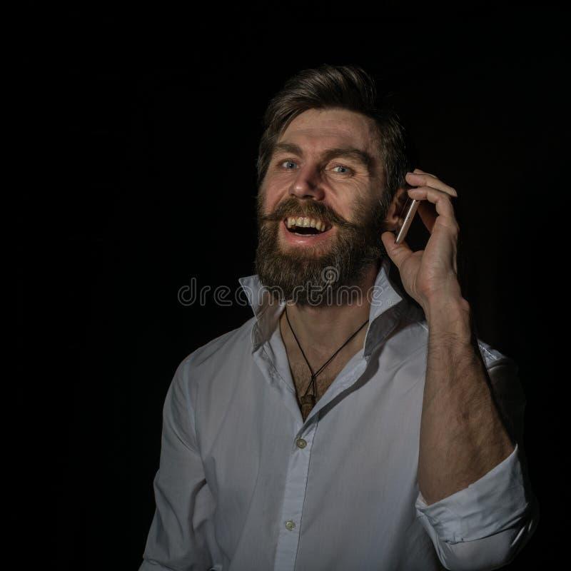 Stilig skäggig man som använder hans telefon med leende på en mörk bakgrund arkivfoton