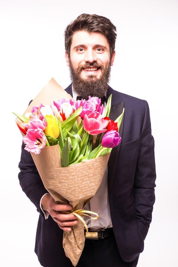 Stilig skäggig man som bär i dräkt, med skägget och den trevliga buketten av blommor arkivfoto