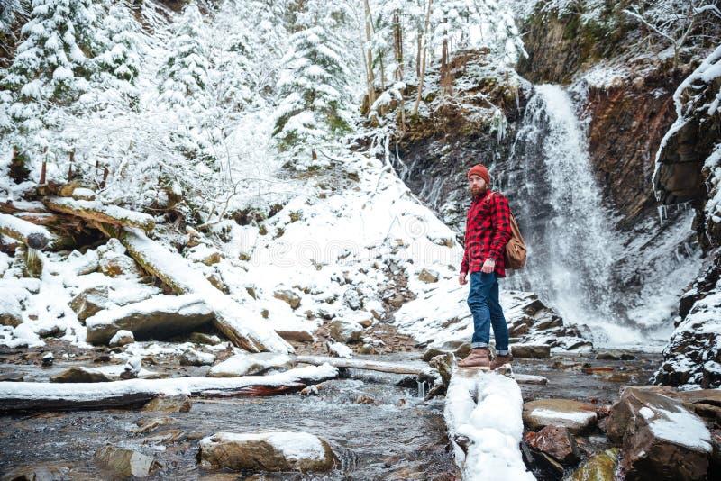 Stilig skäggig man som går nära vattenfallet i vinterskog arkivfoto