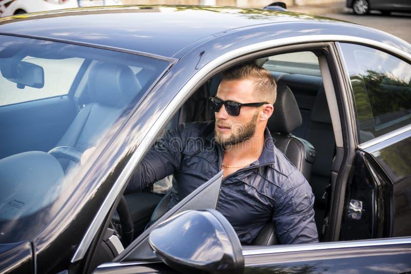 Stilig skäggig man som går ut ur bilen i solglasögon arkivbild