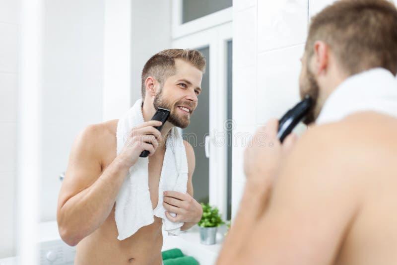 Stilig skäggig man som klipper hans skägg med en beskärare royaltyfria foton