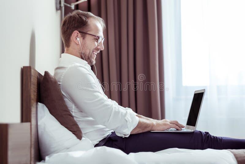 Stilig skäggig man som ler, medan hålla ögonen på komedi på bärbara datorn arkivbilder