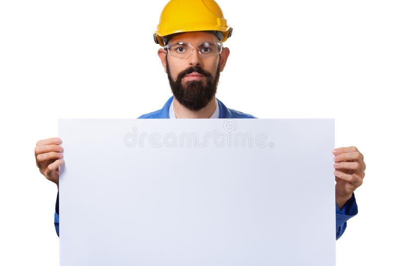 Stilig skäggig manarbetare i den skyddande hjälmen som rymmer det vita annonserande banret med kopieringsutrymme som isoleras p arkivbilder