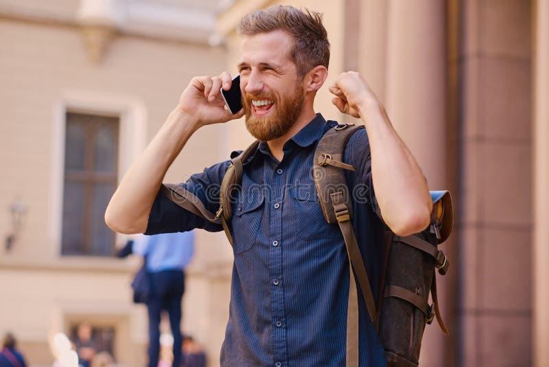 Stilig skäggig manlig turist, i tillfällig kläder och påsesamtal royaltyfri fotografi