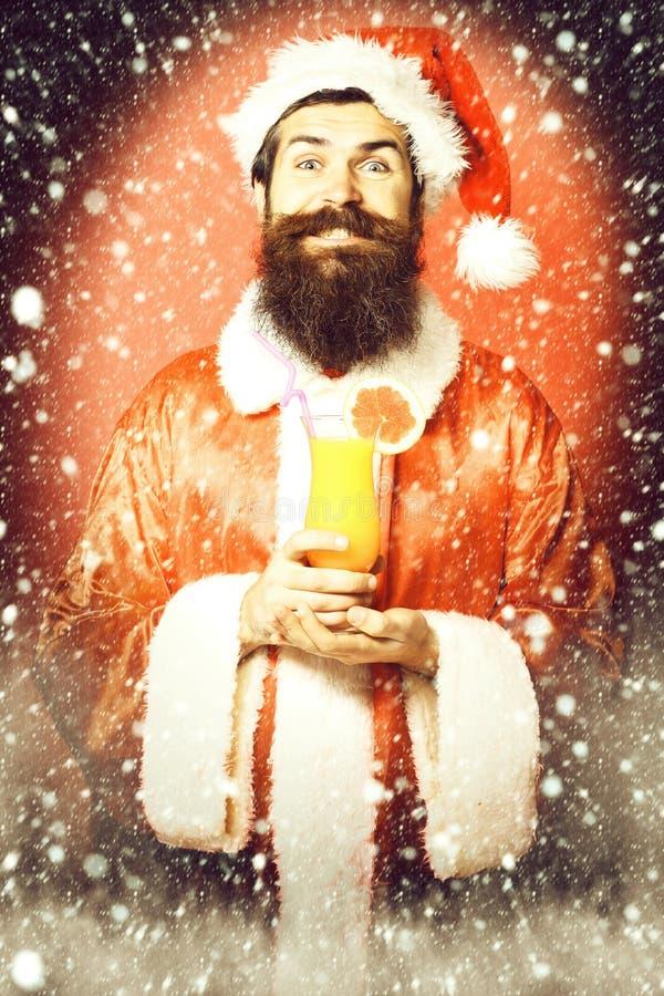 Stilig skäggig Santa Claus man med det långa skägget på att le hållande exponeringsglas för framsida av den nonalcoholic coctaile royaltyfria bilder