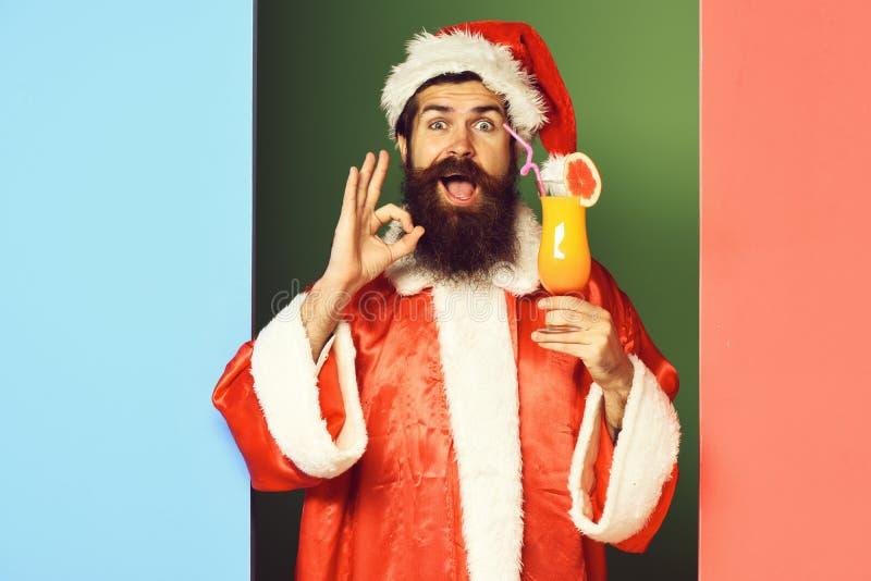 Stilig skäggig Santa Claus man med det långa skägget på att le hållande exponeringsglas för framsida av den nonalcoholic coctaile royaltyfri fotografi