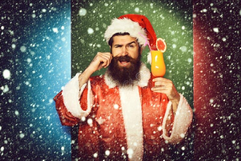 Stilig skäggig Santa Claus man med det långa skägget på att le hållande exponeringsglas för framsida av den nonalcoholic coctaile fotografering för bildbyråer
