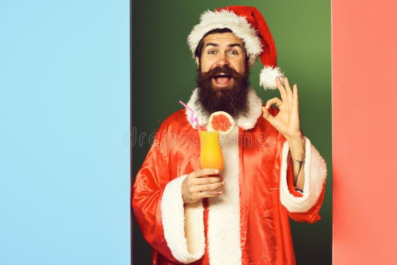 Stilig skäggig Santa Claus man med det långa skägget på att le hållande exponeringsglas för framsida av den nonalcoholic coctaile arkivfoton