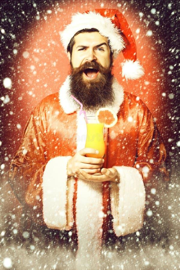 Stilig skäggig Santa Claus man med det långa skägget på att le hållande exponeringsglas för framsida av den nonalcoholic coctaile arkivbild