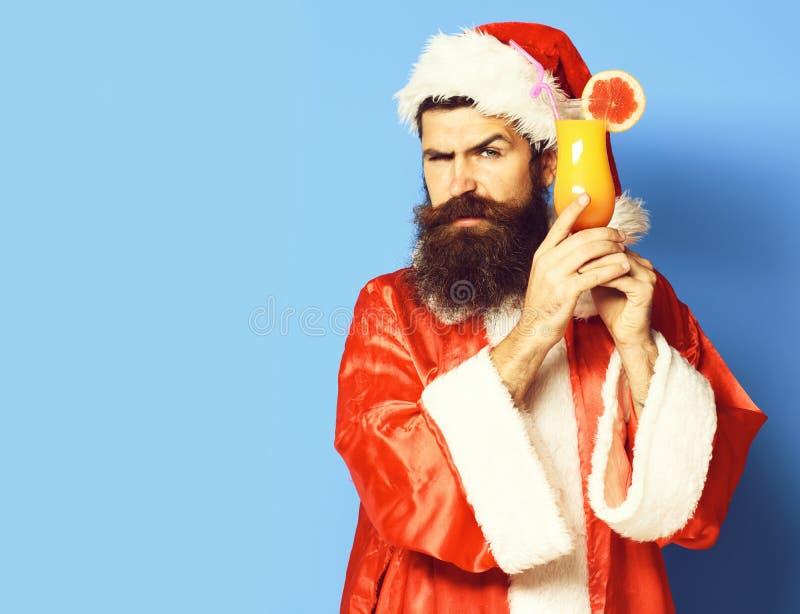 Stilig skäggig Santa Claus man med det långa skägget på den allvarliga framsidan som rymmer exponeringsglas av den nonalcoholic c fotografering för bildbyråer