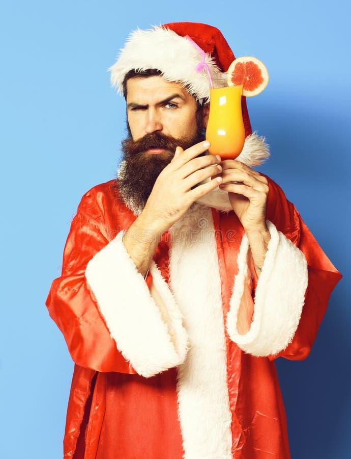 Stilig skäggig Santa Claus man med det långa skägget på den allvarliga framsidan som rymmer exponeringsglas av den nonalcoholic c royaltyfria bilder