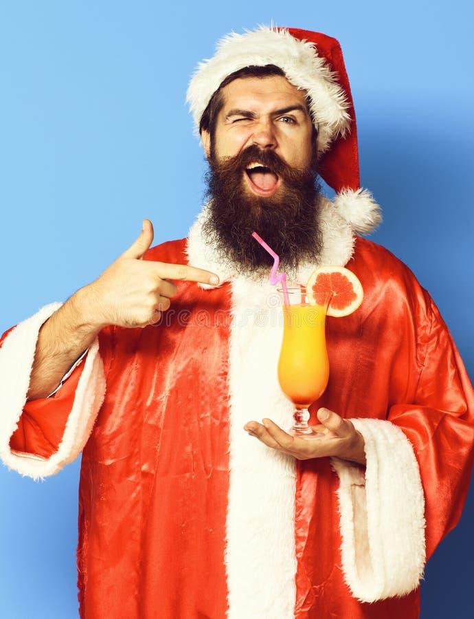 Stilig skäggig Santa Claus man med det långa skägget på den roliga framsidan som rymmer exponeringsglas av den nonalcoholic cocta fotografering för bildbyråer