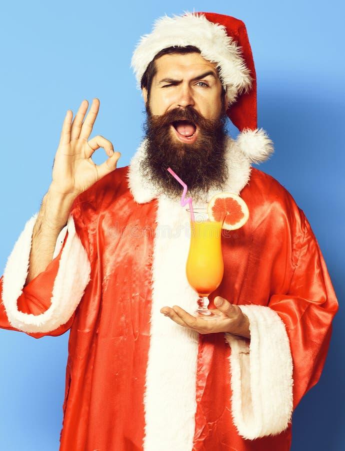 Stilig skäggig Santa Claus man med det långa skägget på den roliga framsidan som rymmer exponeringsglas av den nonalcoholic cocta royaltyfria bilder