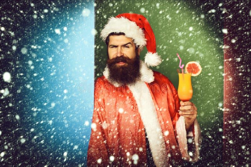 Stilig skäggig Santa Claus man med det långa skägget på den roliga framsidan som rymmer exponeringsglas av den nonalcoholic cocta arkivfoto