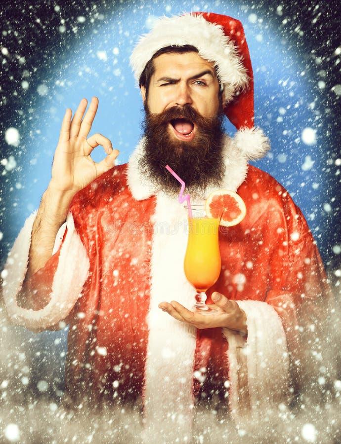 Stilig skäggig Santa Claus man med det långa skägget på den roliga framsidan som rymmer exponeringsglas av den nonalcoholic cocta arkivbilder