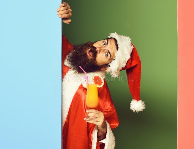 Stilig skäggig Santa Claus man med det långa skägget på den roliga framsidan som rymmer exponeringsglas av den nonalcoholic cocta arkivfoton