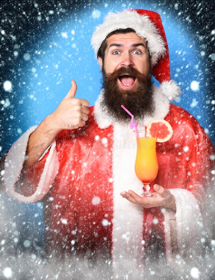Stilig skäggig Santa Claus man med det långa skägget på den roliga framsidan som rymmer exponeringsglas av den nonalcoholic cocta royaltyfri fotografi