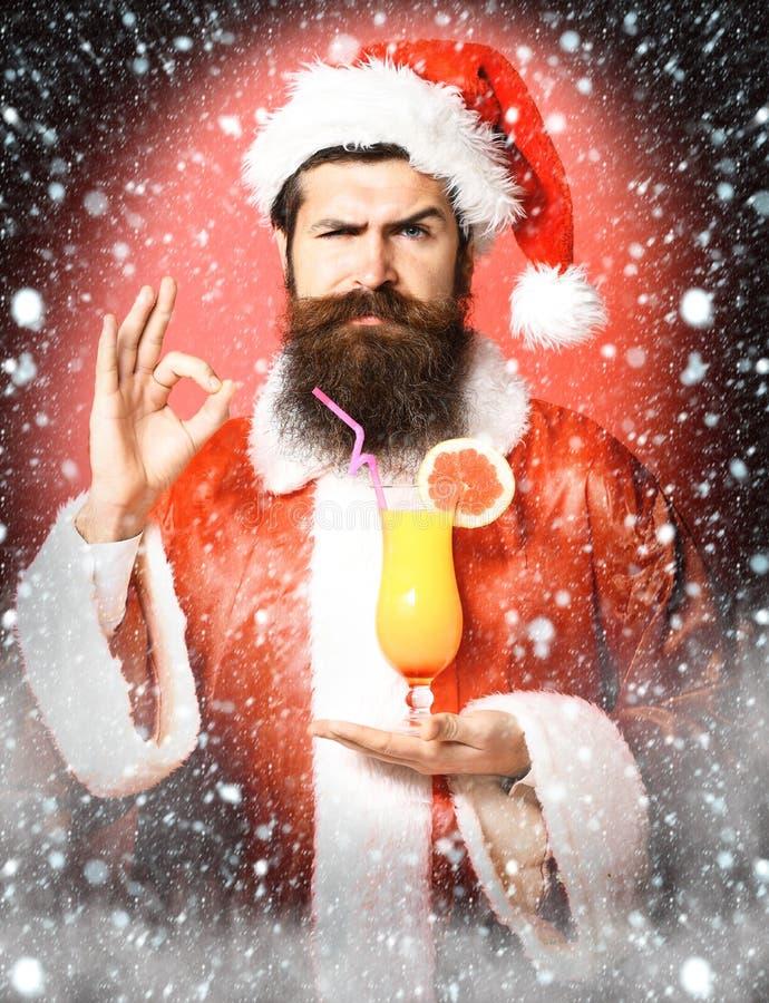 Stilig skäggig Santa Claus man med det långa skägget på hållande exponeringsglas för allvarlig framsida av den nonalcoholic cocta arkivbilder