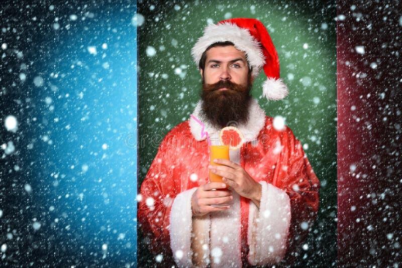 Stilig skäggig Santa Claus man med det långa skägget på hållande exponeringsglas för allvarlig framsida av den nonalcoholic cocta royaltyfri fotografi