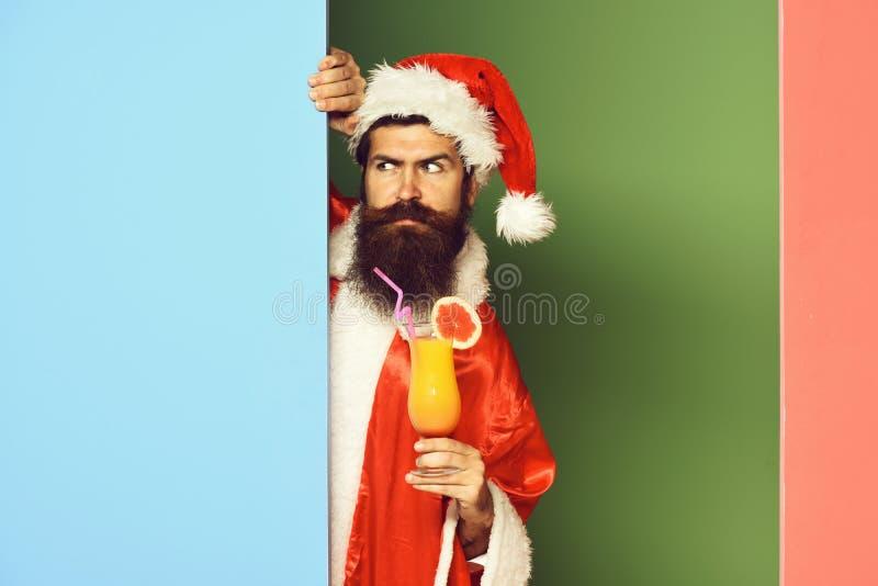 Stilig skäggig Santa Claus man med det långa skägget på hållande exponeringsglas för allvarlig framsida av den nonalcoholic cocta royaltyfri foto