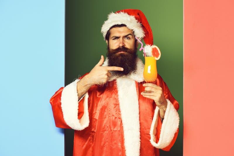 Stilig skäggig Santa Claus man med det långa skägget på hållande exponeringsglas för förvånad framsida av den nonalcoholic coctai royaltyfri foto